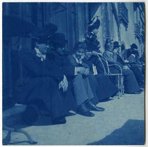 Cyanotype of people sitting on sidewalk