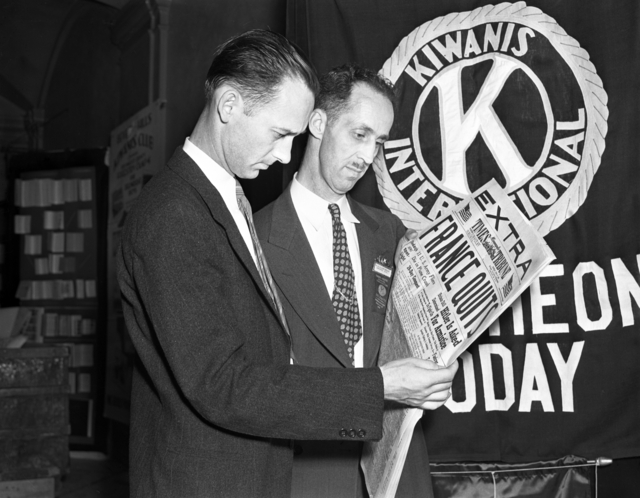 Two men standing and reading the same newspaper