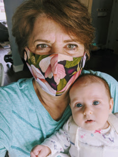 A grandma wears a mask while holding her granddaughter.
