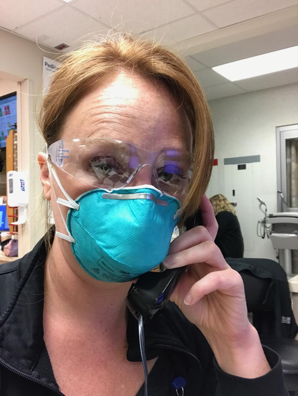 Woman wearing a blue medical mask.