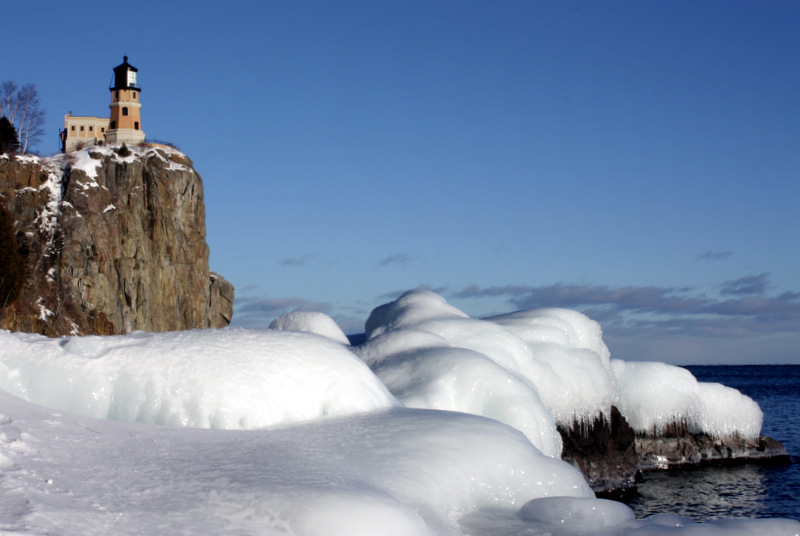 The lighthouse on a cliff at the top left, ice-covered rocks on the lake's edge in the foreground