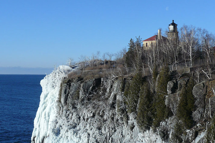 The only spot from the north/east. Cliff in the foreground, with the lightkeeper house and lighthouse visible behind trees.