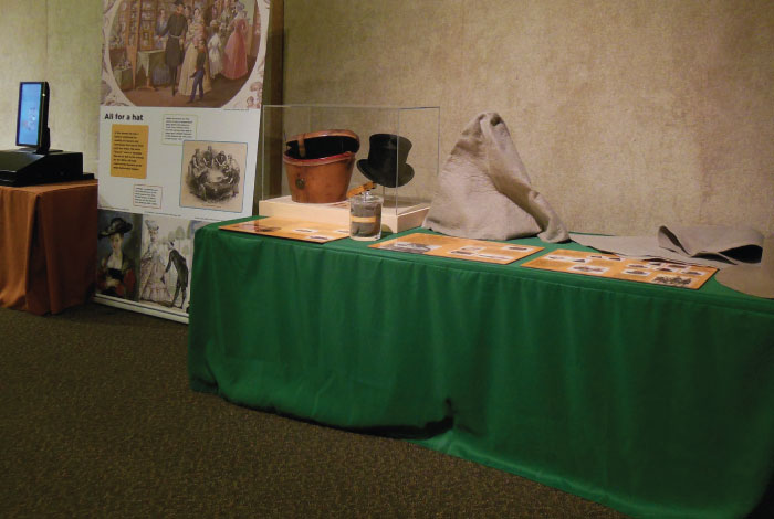 Display board and table with pelts and a hat.
