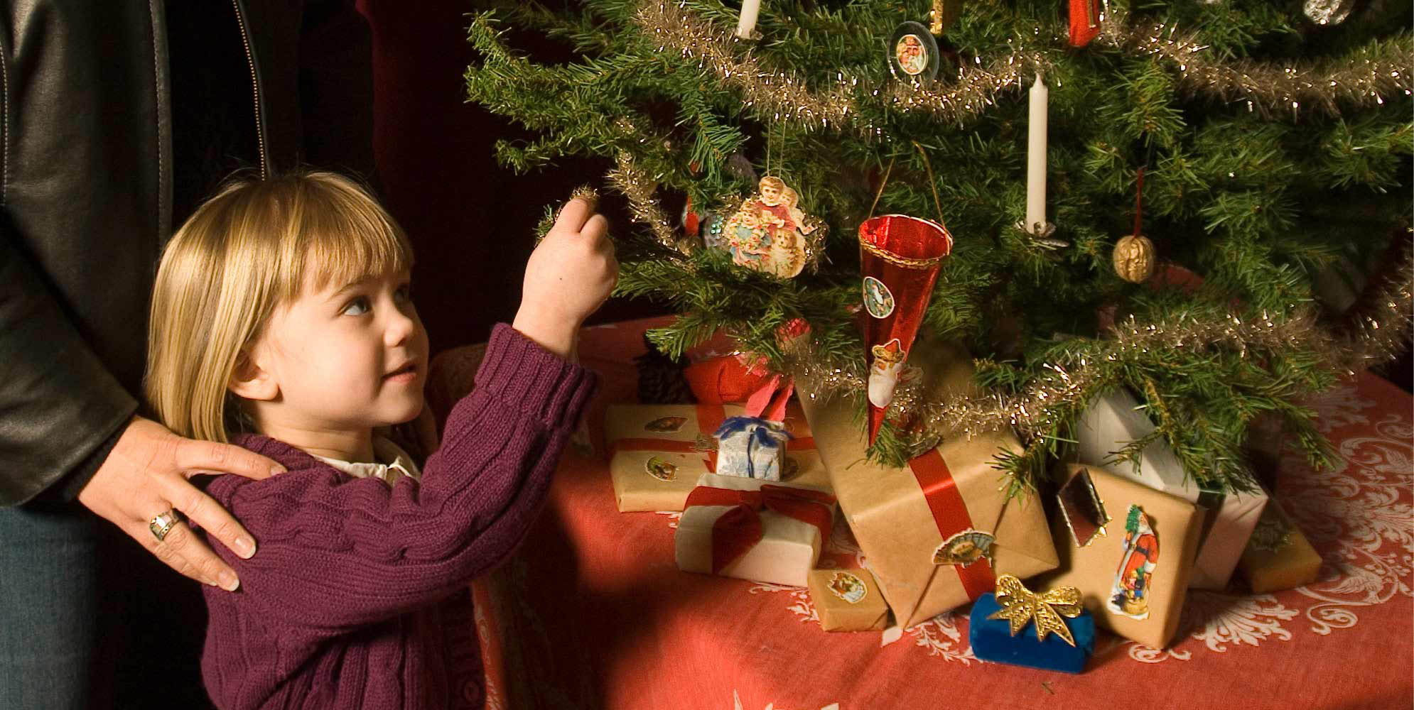 Girl hanging an ornament on a Christmas tree