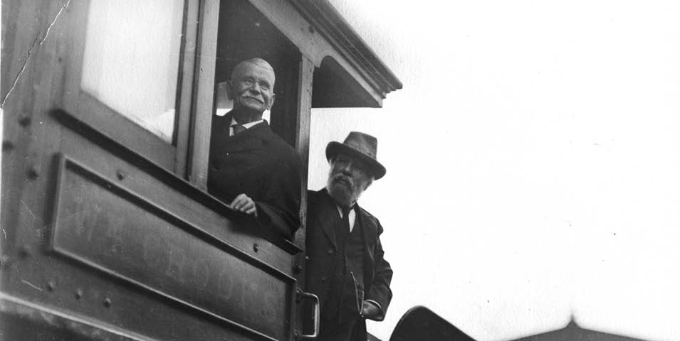 Two men on a train, one is looking out of a window