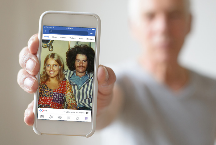 Man holding phone displaying old photo of himself with a woman.