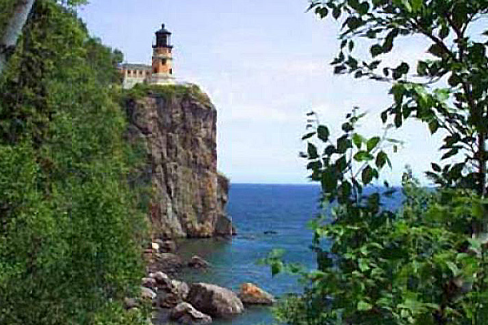 The lighthouse on a cliff, buildings partly obscured, with some trees in the foreground, and part of the lake visible.