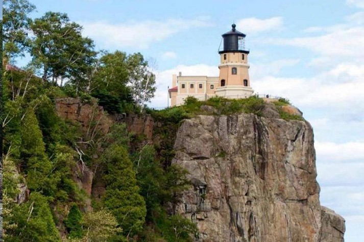 The entire lighthouse and building visible on the cliff.