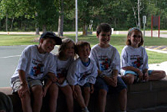 Five kids wearing the same kinds of t-shirts sitting in a park.