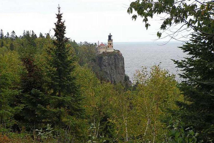The lighthouse and the cliff visible from afar, with lots of trees in the foreground.