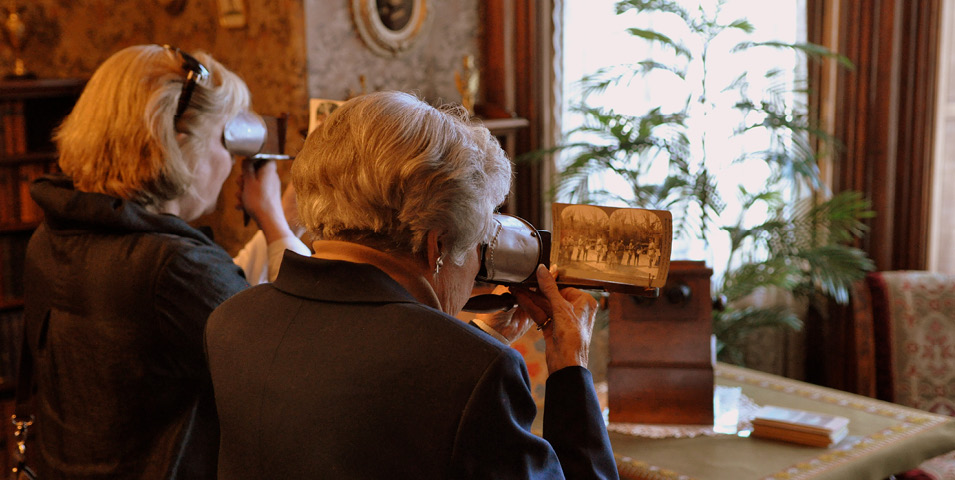 Two women looking at photographs through Holmes stereo viewers