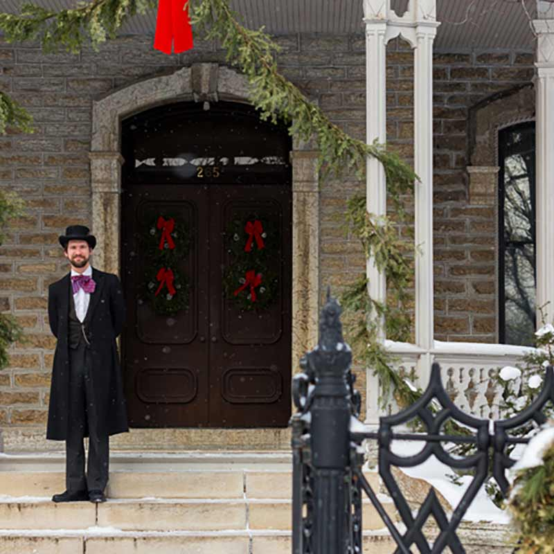 Man in suit and hat on steps of Alexander Ramsey House, with garland and wreath decorations