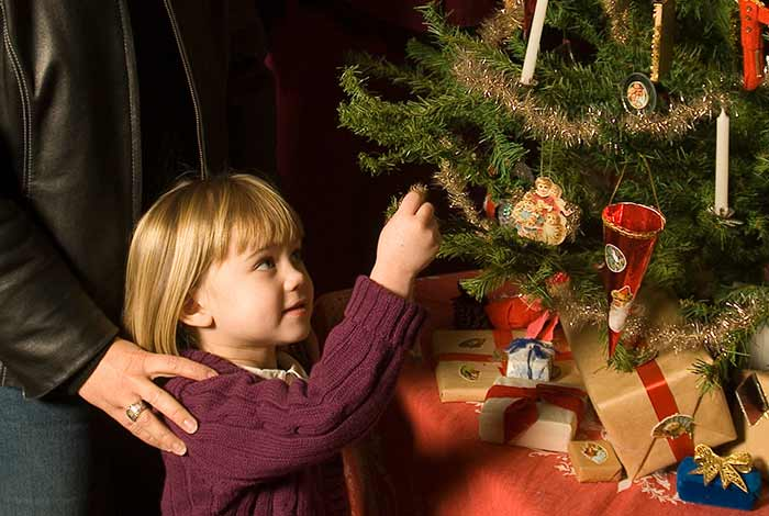 Young girl admiring ornament on a tree