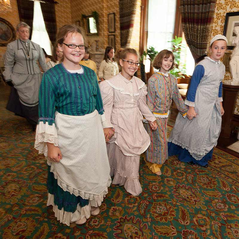 Four young girls dressed in Victorian-era clothing walking in a line
