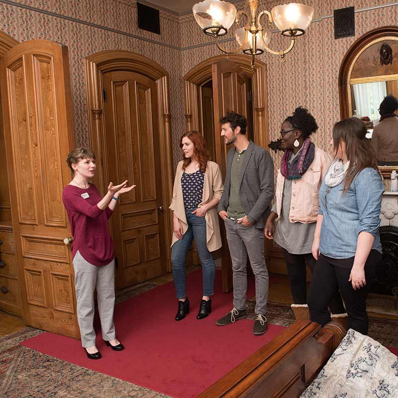 Woman leading tour group through Alexander Ramsey's bedroom
