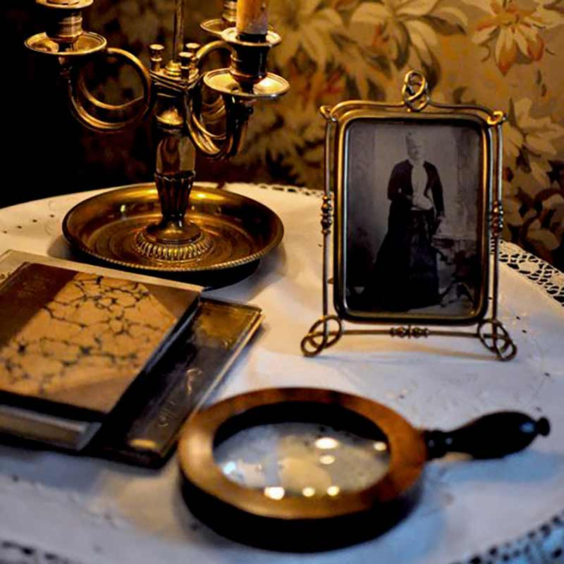 Antique magnifying glass resting on table next to antique photograph in frame