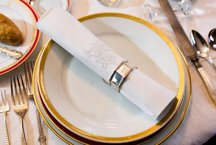 Place setting with cloth napkin with silver napkin ring resting on gold-edged plate