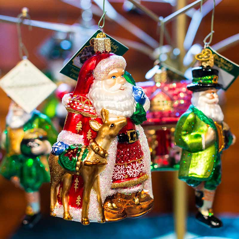 Santa ornament hanging on display with other Christmas ornaments
