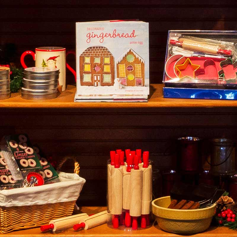 Cookbooks, rolling pins, cookie cutters, and other baking items on shelf