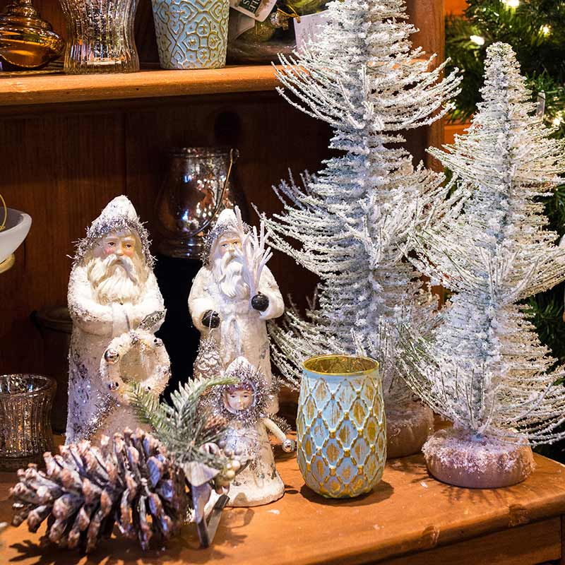 Santa figurines, frosted mini trees and pinecones, on a display shelf