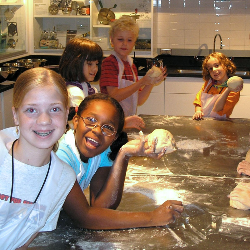 Kids sit around a flour-covered counter in the baking lab holding balls of dough.