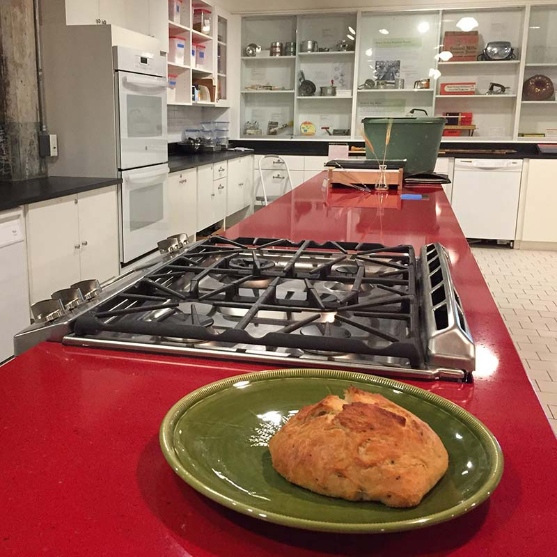 A baked good sitting on a dish next to a stovetop.
