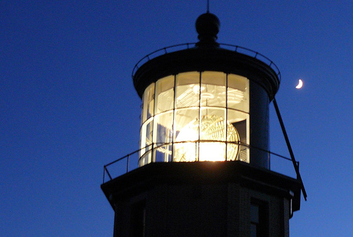 Closeup of the lit beacon with a crescent moon in the background