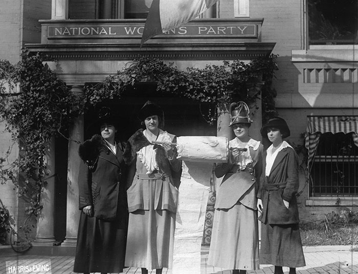 Four women standing with two holding a petition together.