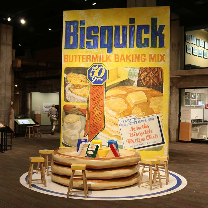A large-scale model of a Bisquick box with a stack of model pancakes.