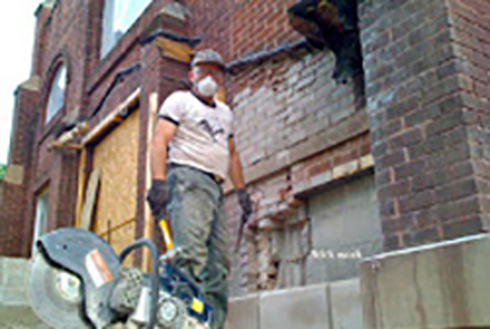 A worker wearing a hat and a mask is working beside a building.