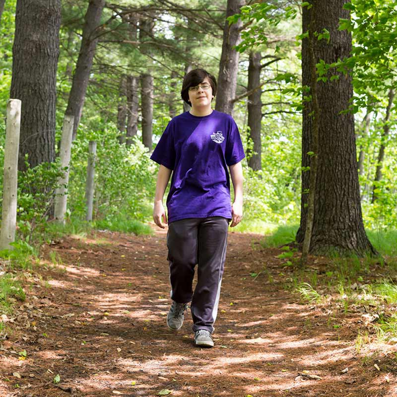 Boy walking on a trail in the woods.