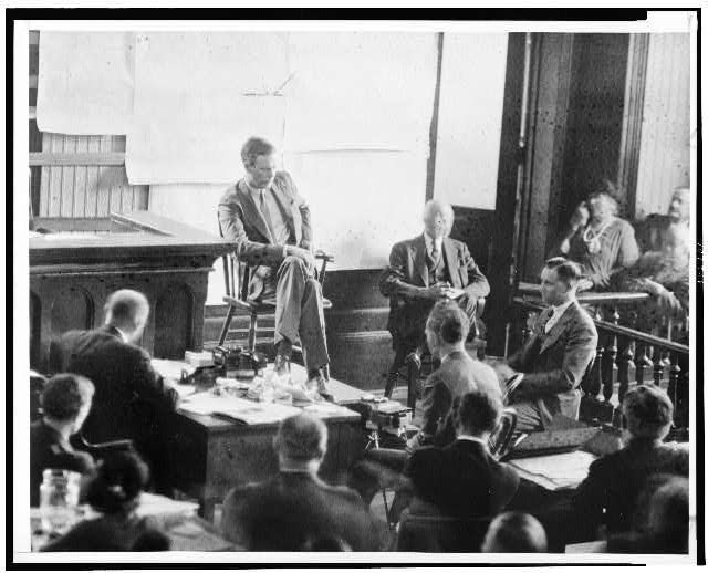 Charles Lindbergh sits on the witness stand in a court room.