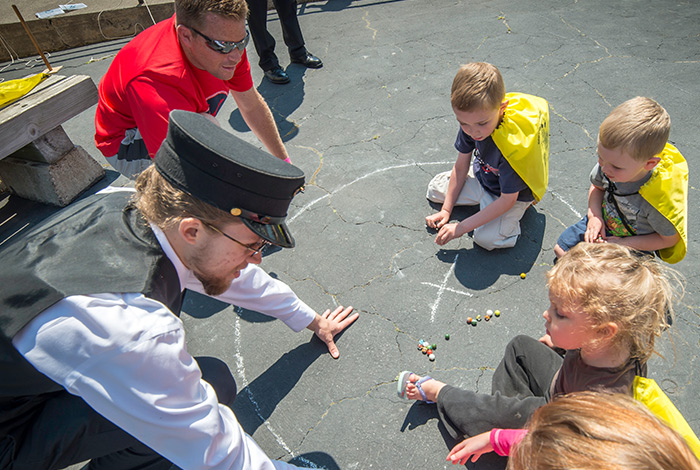 Lighthouse keeper playing marbles with children