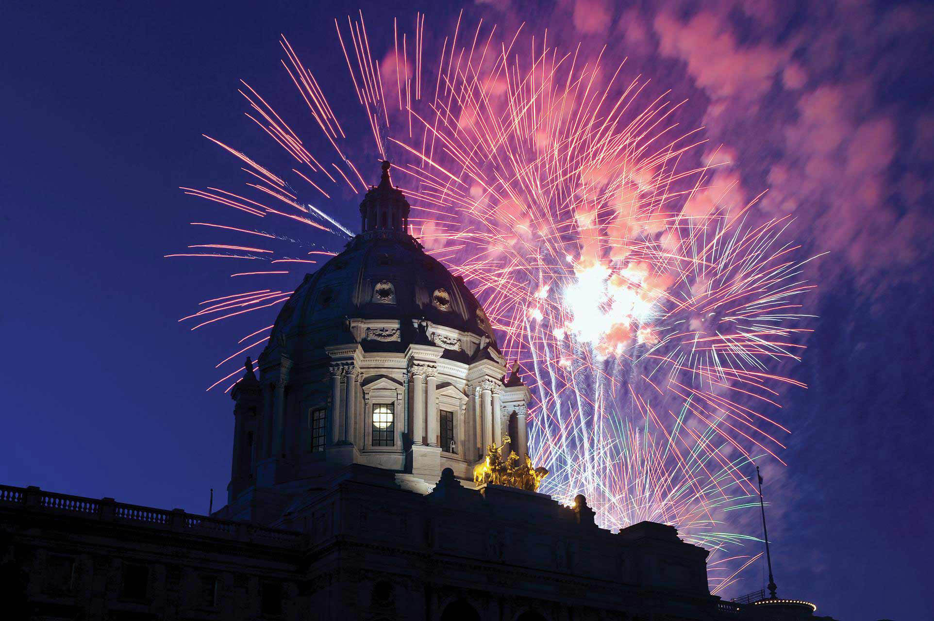pink fireworks to the right of the Capitol dome with a bluish sky