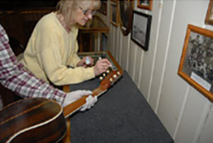 Two people are cataloging a guitar.