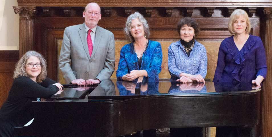 Five musicians, one sitting and the others standing behind a piano