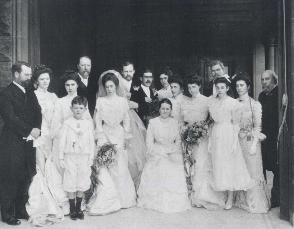 A large group of people dressed up on the back terrace, Charlotte to the left of her mother in the center, and James on the right