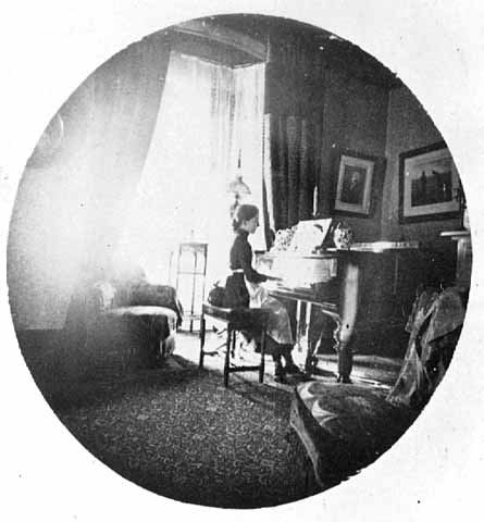 A girl seated at a grand piano in front of a window