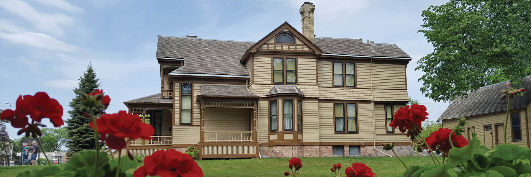 Exterior view of Comstock House against a blue sky and red flowers in foreground.