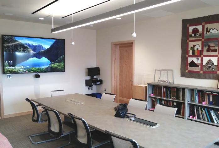 Conference room with rectangular table and video monitor.