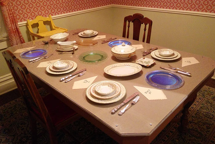 A dining room table with settings for 6 people.