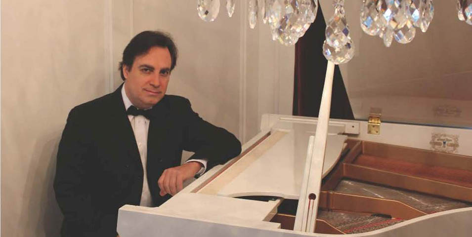 A man sitting at a white grand piano