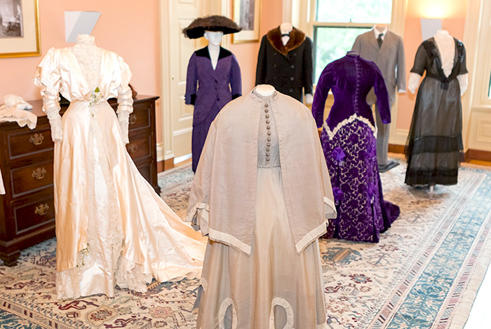 Seven mannequins wearing dresses and suits, posed on a rug