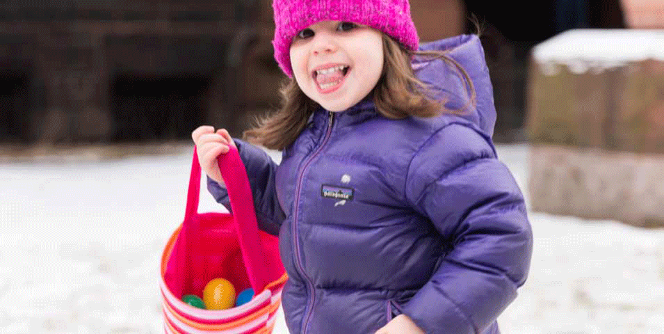 Girl with a wide smile in a snowsuit collecting Easter eggs