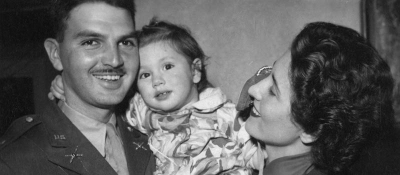 Two parents and a child hugging.