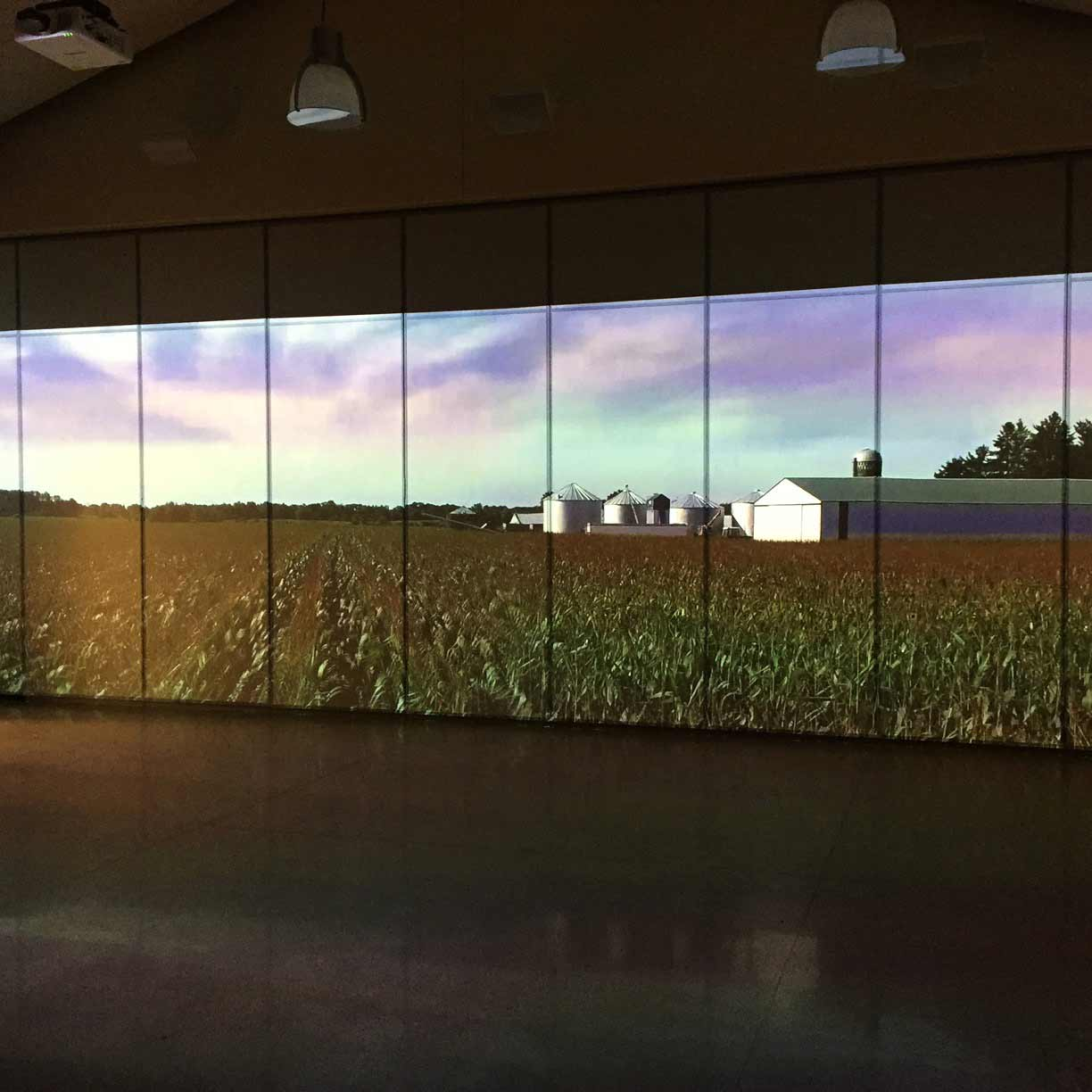 A dark room with a farm scene on a multi-panel screen