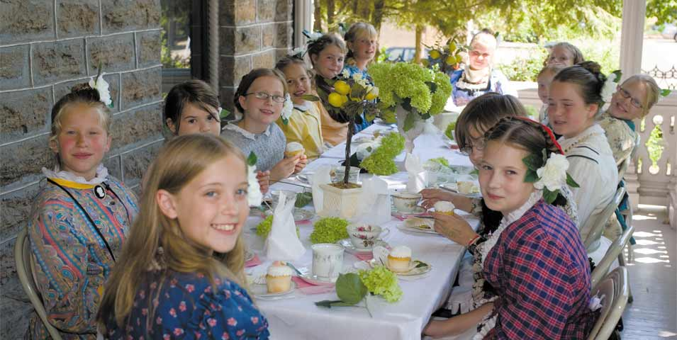 Girls in Victorian dresses sitting at a long table with tea and cupcakes