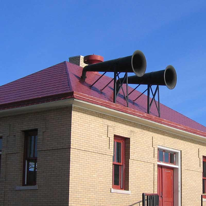 Light-brown building with a red roof and two long, black horns mounted on the roof