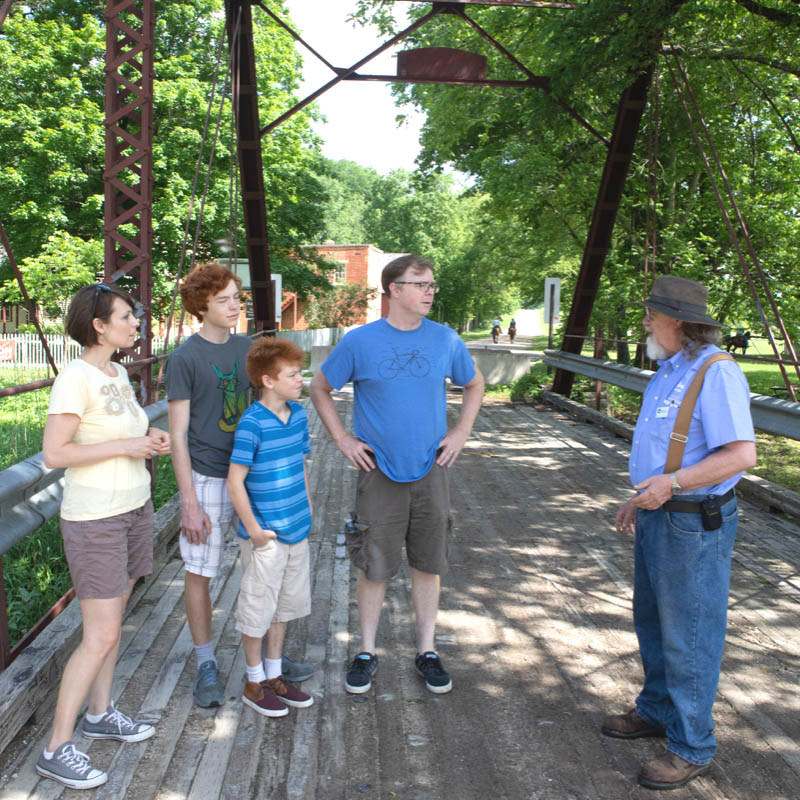 A tour group listens to a guide on an old bridge.