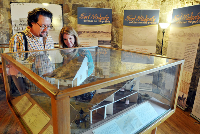 A couple look into a display case showing a model replica of the fort buildings.